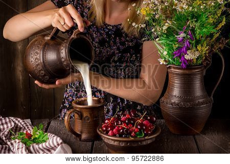The Girl Pouring Milk From A Jug Into A Cup And A Bowl With Berries On A Wooden Table. Jug With Flow