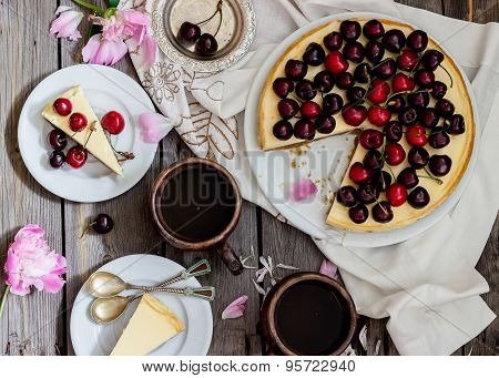 Cheesecake With Cherry, Two Slices On Saucers And Metal Tray  On A Wooden Table. .