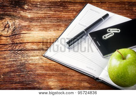 Desktop With Paper Agenda, Smart Phone And Green Apple
