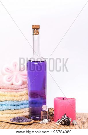 isolated bottle of lavender oil and stack of towels
