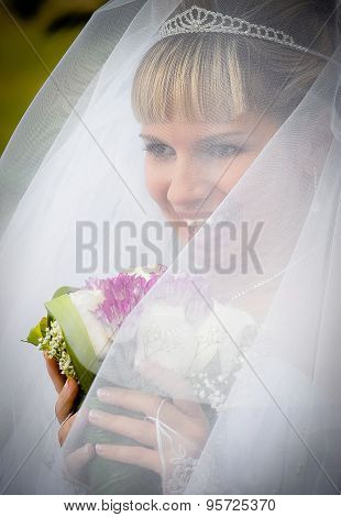 Portrait of  bride with bouquet in the long veil