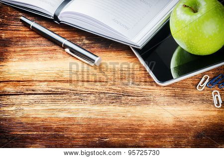 Desktop With Paper Agenda, Digital Tablet And Green Apple