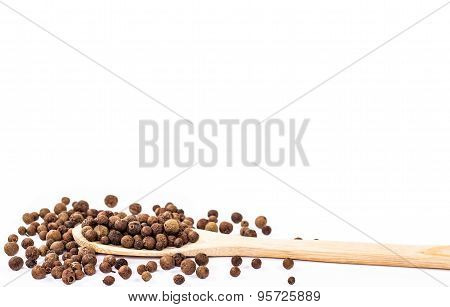 jamaica pepper in wooden spoon isolated on white background.