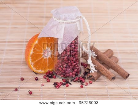red peppercorn in glass, orange and spice on wooden background.
