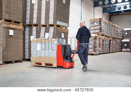 Rear view of male worker pushing handtruck loaded with goods at distribution warehouse