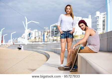 Portrait of confident male and female skateboarders on steps at beach