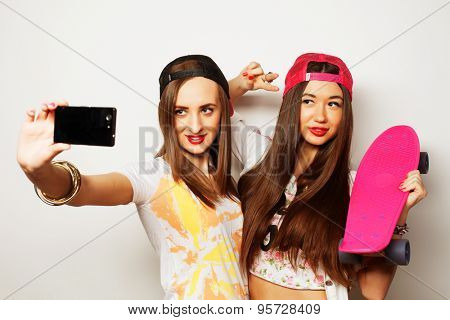 Sporty girlfriends standing having fun together. Beautiful women making selfie.Positive  emotion. White background.