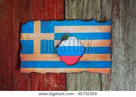 russian flag behind burnt Greek flag background