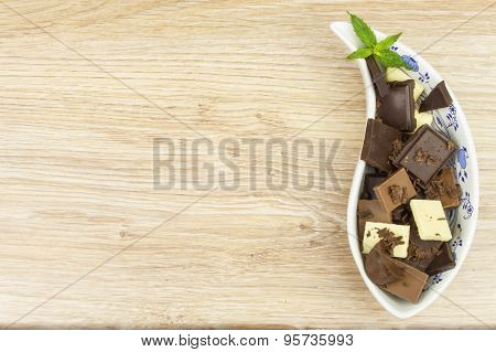 We love chocolate. Chocolate in a porcelain bowl on the table.