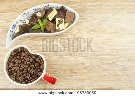 We love coffee and chocolate. Chocolate and coffee on a wooden table.
