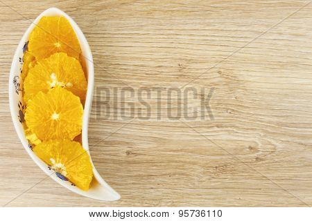 peeled and sliced orange in a porcelain bowl on the table.