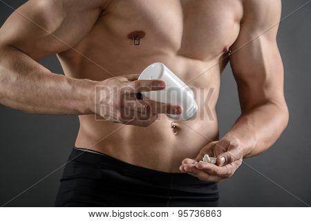 Muscular Man Taking His Supplement Pills