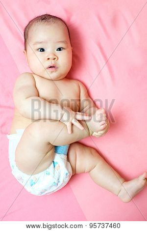 Asian Baby Girl Touching Her Foot