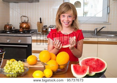 Happy girl eating fruit at a table, concept of health care and healthy child nutrition. Child with o