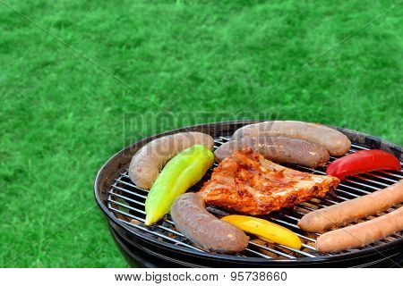 Hot Bbq Grill With Assorted Meat On The Garden Lawn
