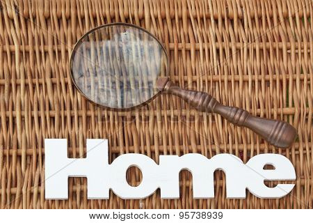 Wood Sign Home And Magnifying Glass On Rustic Wicker Background