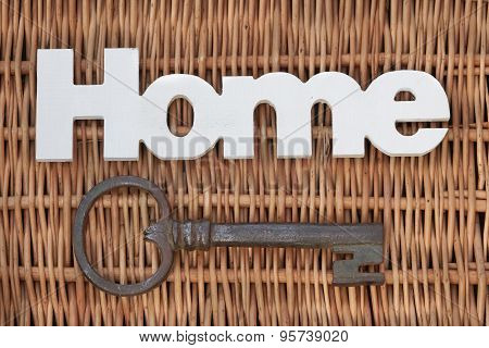 Wood Sign Home And Old Key On Rustic Wicker Background