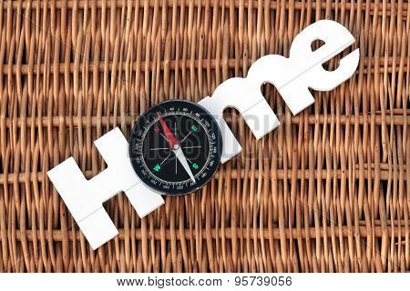 Wood Sign Home And Compass On Wicker Background