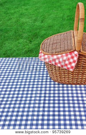 Outdoor Rustic Picnic Table With Hamper And Blue Tablecloth