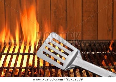 Spatula Close-up On The Hot Flaming Bbq Grill