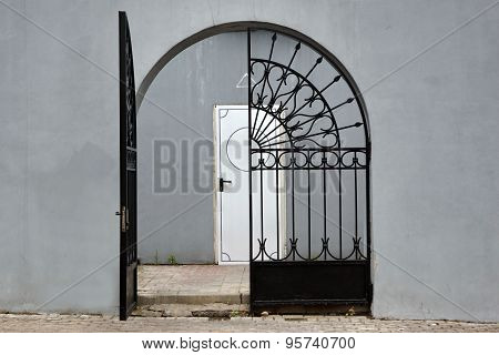 Grey Wall With Iron Gate And Door In The Background
