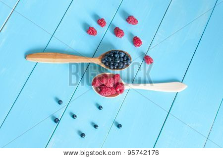 Fresh blueberries and raspberries in wooden spoon. Light blue wood background