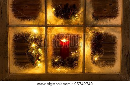 Snow Covered Window With Glowing Candle And Decorative Christmas Wreath On Window