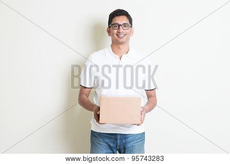Indian man smiling and holding a courier box standing on plain background with shadow. Asian handsome guy model.