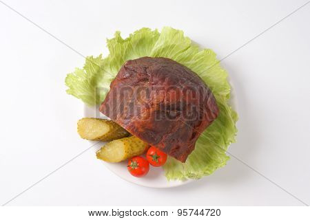 chunk of roasted pork with vegetable garnish on white plate