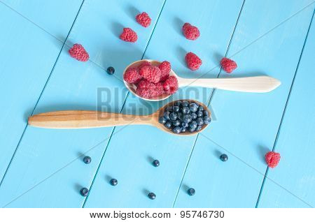 Berries on light blue wooden background. Blueberries and raspberries