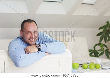 Handsome business man smile into camera in office