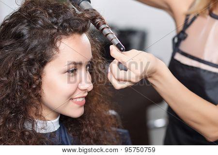 Nice hairdresser holding curling