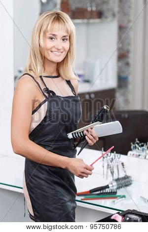 Hairdresser holding hairstyling devices