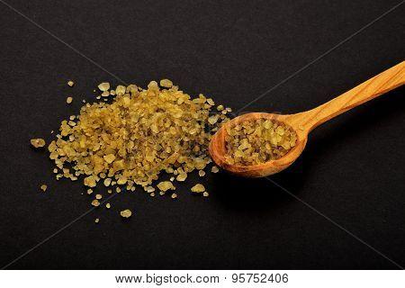 Handful Of Green Hawaiian Salt With Wooden Spoon On Black