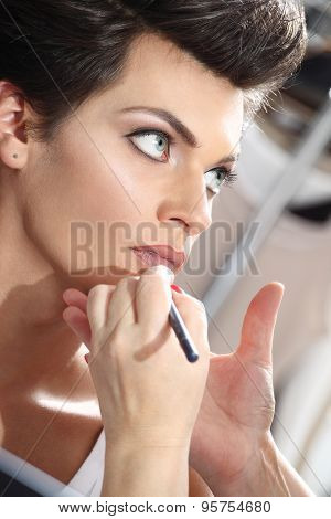 beautiful model having lip liner applied by makeup artist