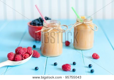 Homemade Banana smoothie in jam jar on light wooden background. Fresh rastberries, blueberries at bl