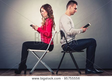 Couple Using Mobile Phones Not Talking. Conflict.