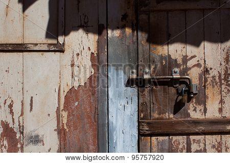 Old worn wooden door locked
