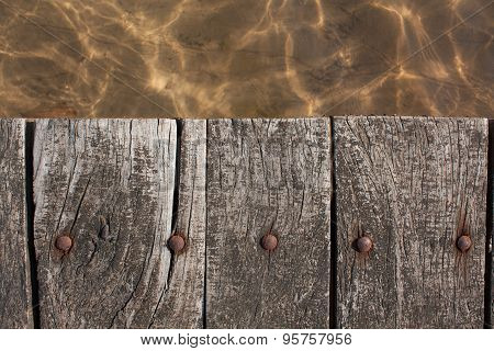 old wood boards of a pier over lake. Close up