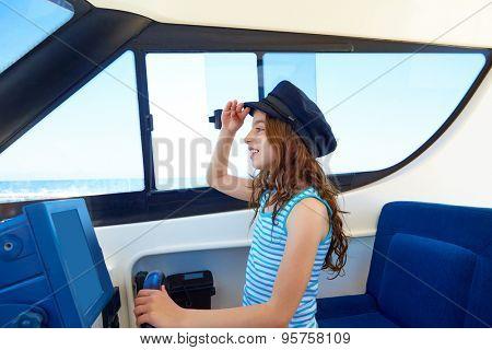 Kid girl pretending be a captain sailor cap in boat indoor holding wheel