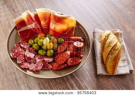 Tapas of Spain with ham bread olives sausage and chorizo on wooden background