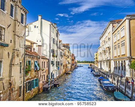 Narrow Canal Lined With Low Rise Buildings, Iconic Canal Scene In Venice, Italy