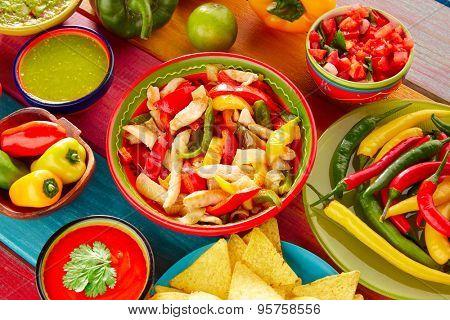 Chicken fajitas with mexican food guacamole pico de gallo chili peppers sauce and nachos