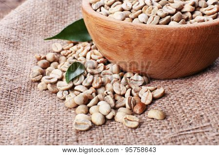 Wooden bowl of green coffee beans on sackcloth, closeup