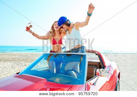 Beautiful party friend girls dancing in a car on the beach happy