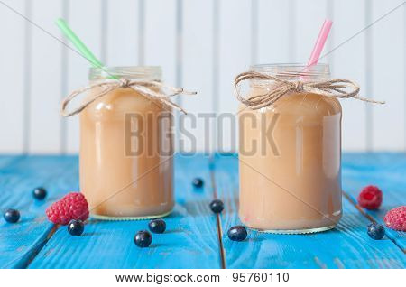 Peach and banana milkshake in mason jar with fresh raspberry, strawberry on the background of blue w