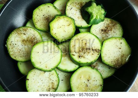 Sliced zucchini in pan on table, closeup