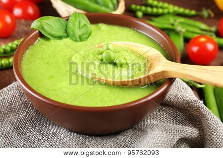Tasty peas soup and cherry tomatoes on table close up