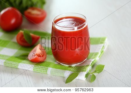 Tomato juice and fresh tomatoes on wooden table close-up