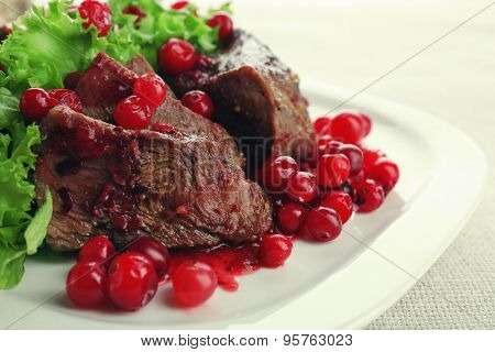 Tasty roasted meat with cranberry sauce on plate, on light background